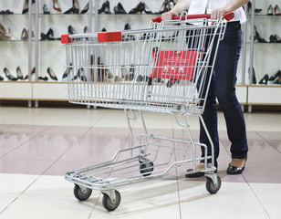 Woman in jeans pushing a shopping cart in a shoe store