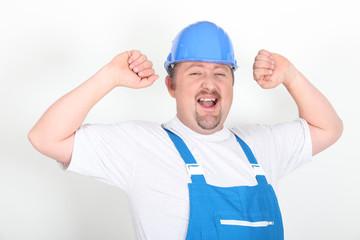 Portrait d'un ouvrier levant les bras sur fond blanc