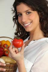 Jeune femme avec corbeille de légumes