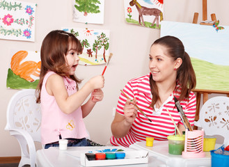 Little girl painting with teacher in preschool.