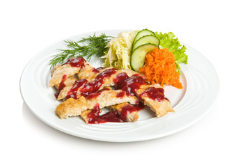 Sliced pork chop with cowberry sauce and vegetable side dish.