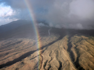 Rainbow hangs over Maui modern windmills