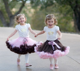 twin toddler girls in pretty skirts laughing