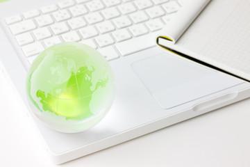 緑の地球と白いノートパソコンとメモ帳
