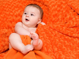 bambino che gioca con una coperta arancione