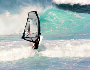 Male windsurfer in active waves