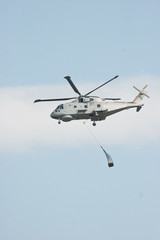 Merlin Helicopter Lifting Cargo Against Blue Sky