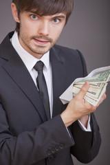 businessman holding dollars in envelope