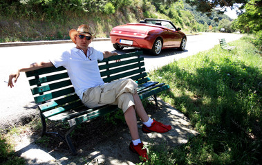 Fashion man with car on vacation in Corsica, France