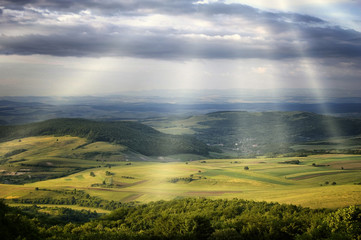 sun rays over green hills in a beautiful summer day