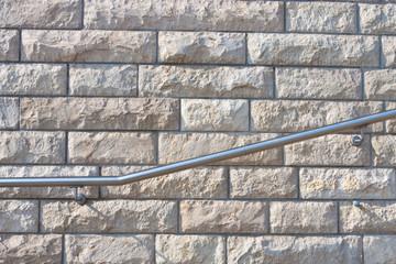 Steinwand mit Handlauf aus Edelstahl