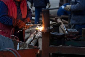 worker inside factory cut metal using blowtorch