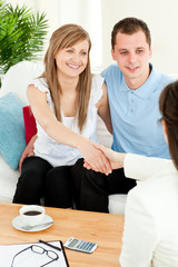 Happy couple concluding a car contract with a female dealer