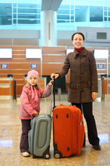 mother and little girl with suitcases standing at airport