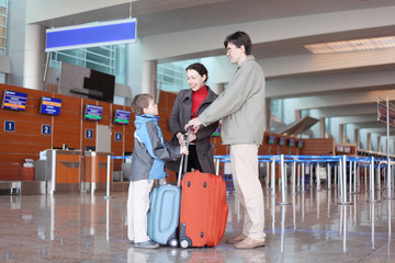 amily with boy standing in airport hall with suitcases
