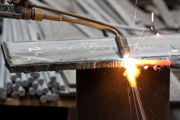 blowtorch cutting metal in factory and sparks