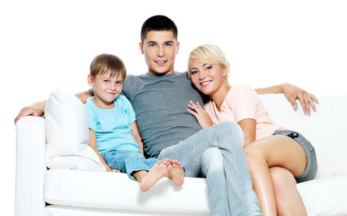 Beautiful happy young family with kid on sofa. Isolated