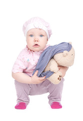 Young child poses with a soft toy on a white background