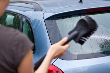 Junge Dame wäscht Auto mit Schlauch