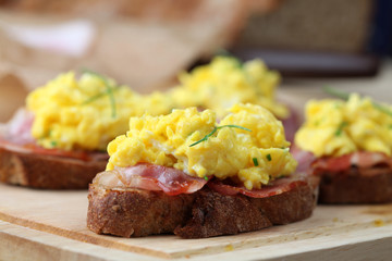 Sandwiches with scrambled eggs and bacon, garnished with chives