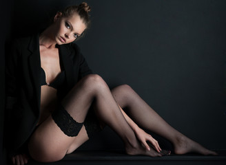 Photography models posing in stockings and sitting on a blackboa