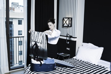Woman packing suitcase in a hotel bedroom
