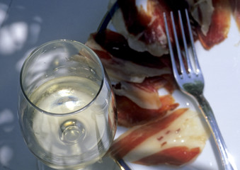 Decorativ table with ham and a glass of vine.
