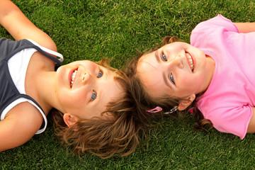 Fototapeta Two smiling girl lying on the grass obraz