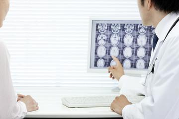 モニターで患者に説明する医師