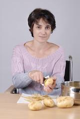 femme handicapé dans chaise roulante pelant des pommes de terre