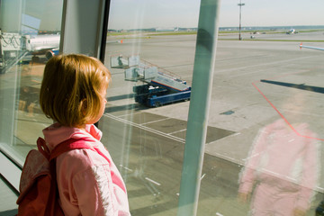 The girl looks out of the window the airport on an airfield