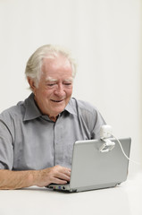 Älterer Herr mit Netbook und Webcam