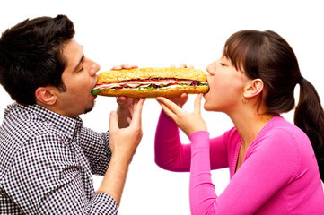 young man and a woman eating sandwich from two sides