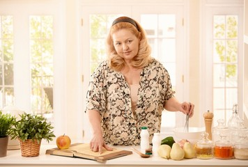 Woman checking recipe in kitchen