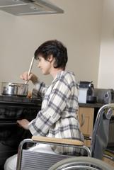 femme handicapé preparant le diner dans la cuisinte