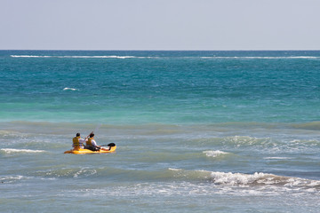 Couple Paddling out to Sea