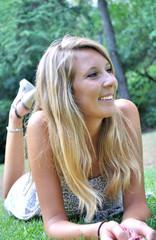 Femme souriante à plat ventre dans l'herbe
