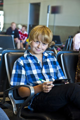 boy is waiting for departure at the airport