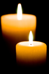 Close up of two lit white candles on black background.