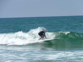 Surfer riding waves on Oceanside Harbor Beach