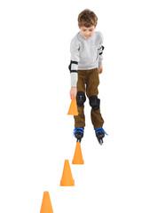 boy with cone in hand rollerblading near orange cones