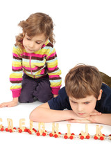little serious boy and girl playing with wooden railway