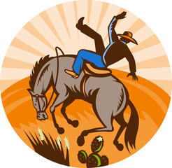 Rodeo cowboy falling off horse in desert