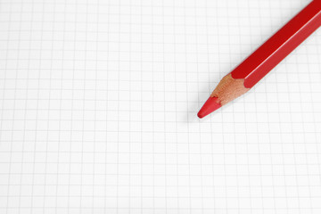 Roter Buntstift auf kariertem Papier