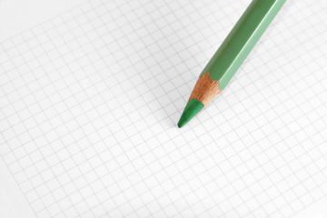 Grüner Stift auf kariertem Papier