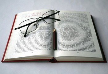 Open book, glasses and pencil