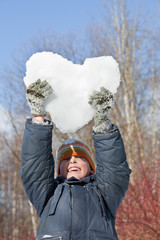 boy keeps in hands hearts from snow in winter
