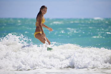 teenage girl in a yellow bikini surfing in Hawaii