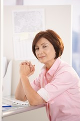 Portrait of mature office worker sitting at desk