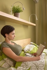 Mid-adult woman reading in bed